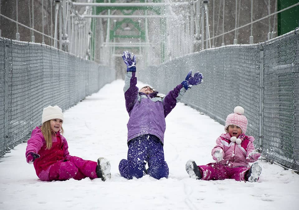 Three young girls in snowsuits play in the snow