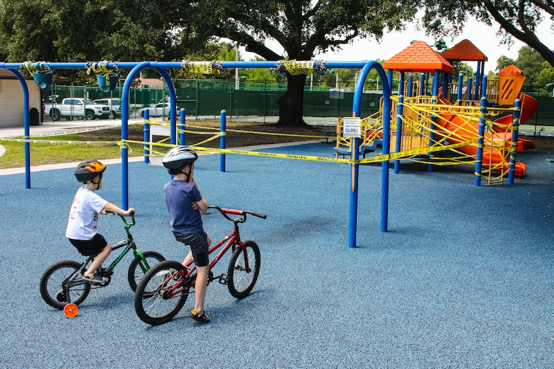 Two young boys ride bikes to the playground.