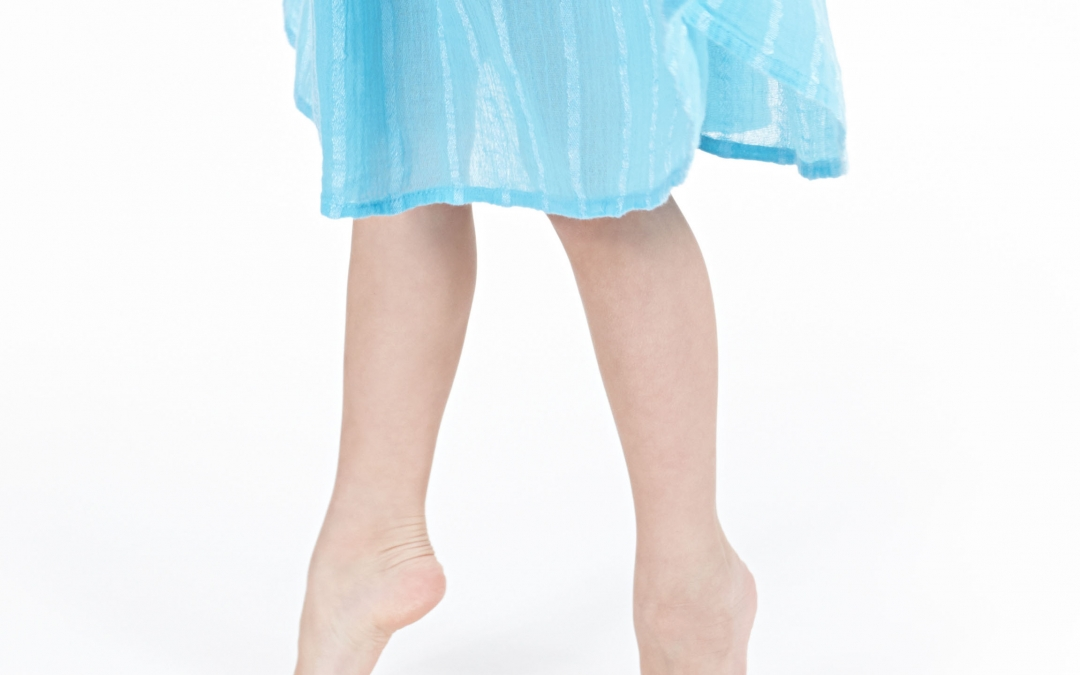 Young girl in blue dress walking on tip toe