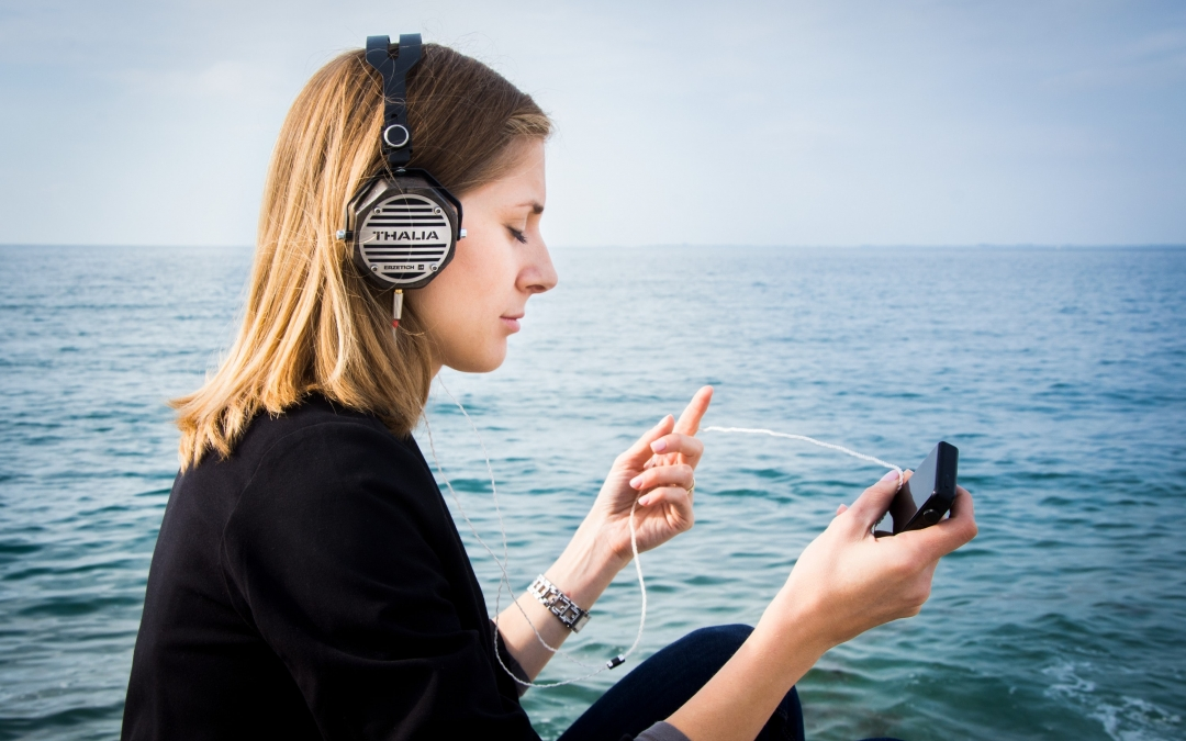 Woman relaxes listening to headphones with ocean in the background