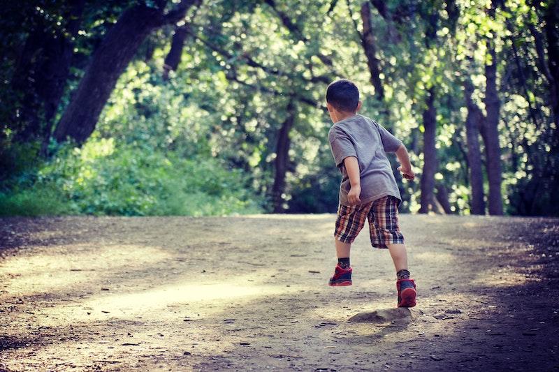 Young boy runs on a dirt road