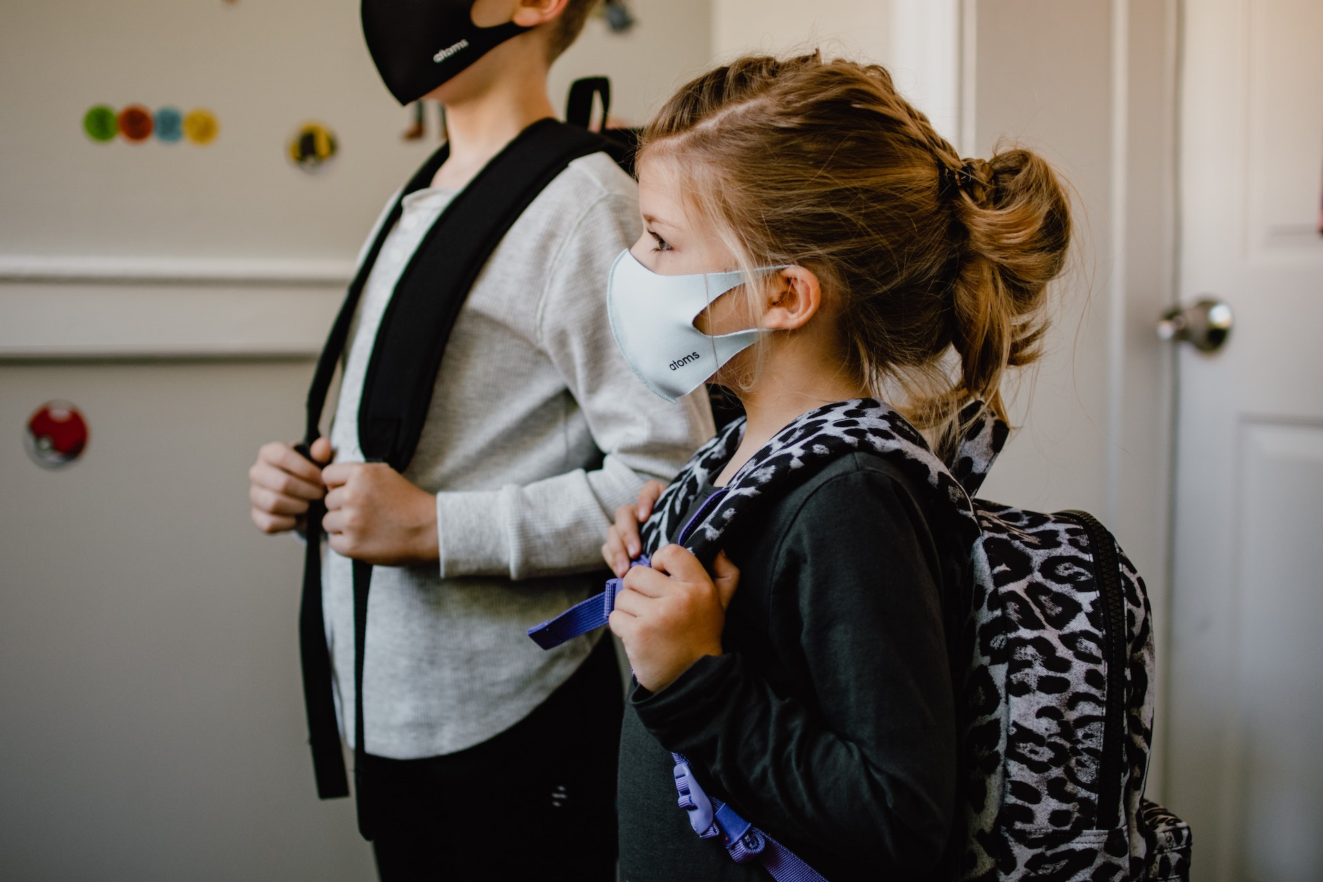 School-aged girl and boy with backpacks wearing masks on the first day of school