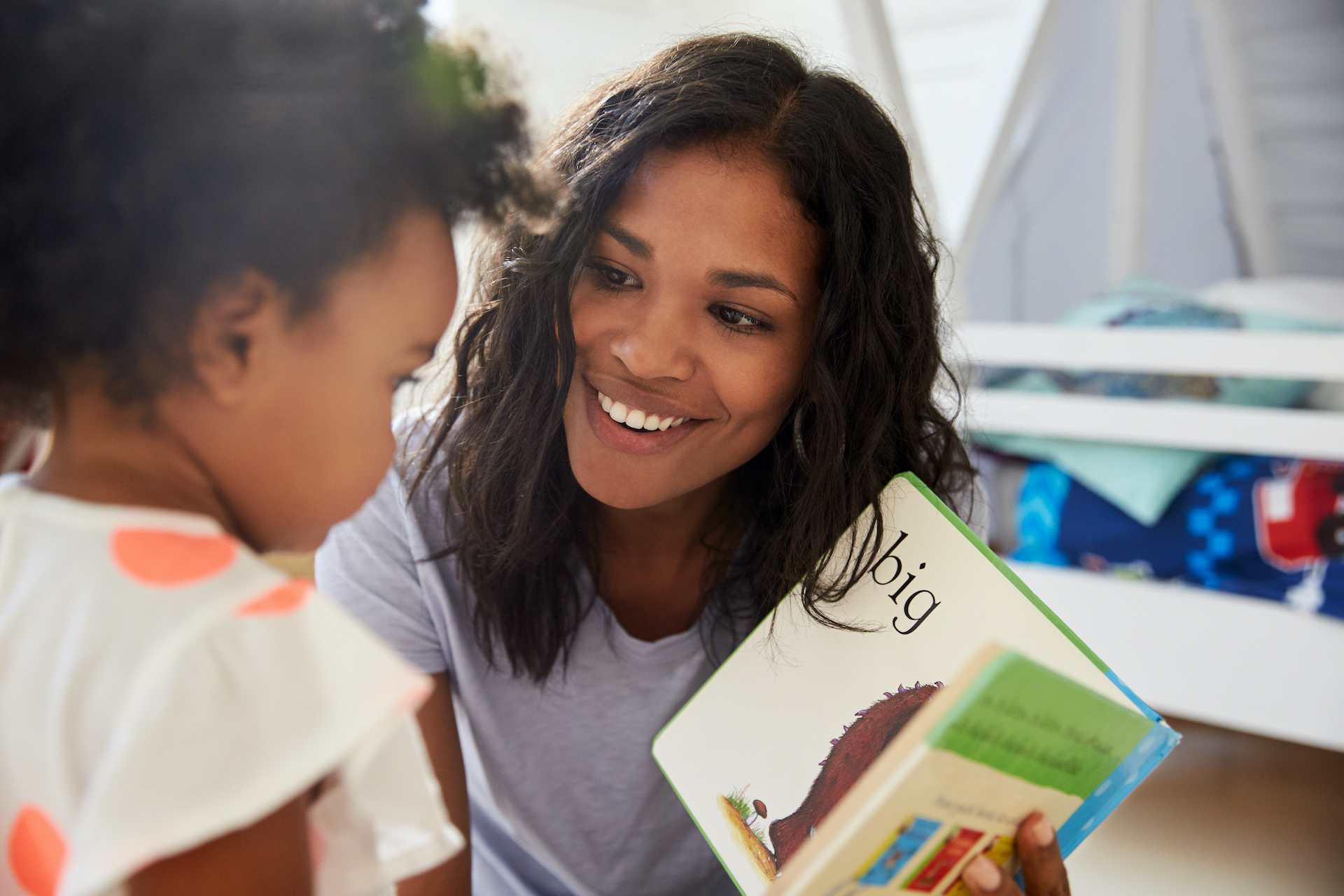 Black mom reads to daughter pointing out words and pictures in playroom