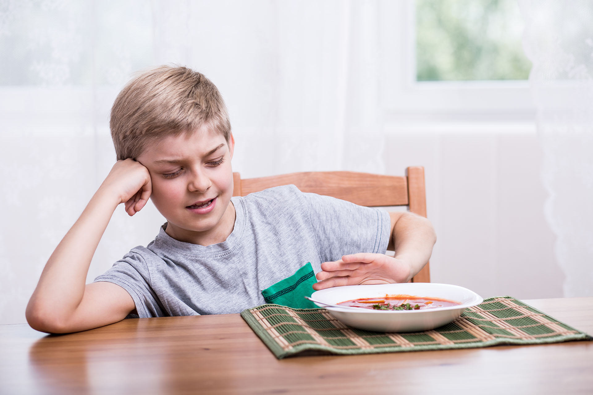 Young boy pushes away bowl of soup at lunchtime.