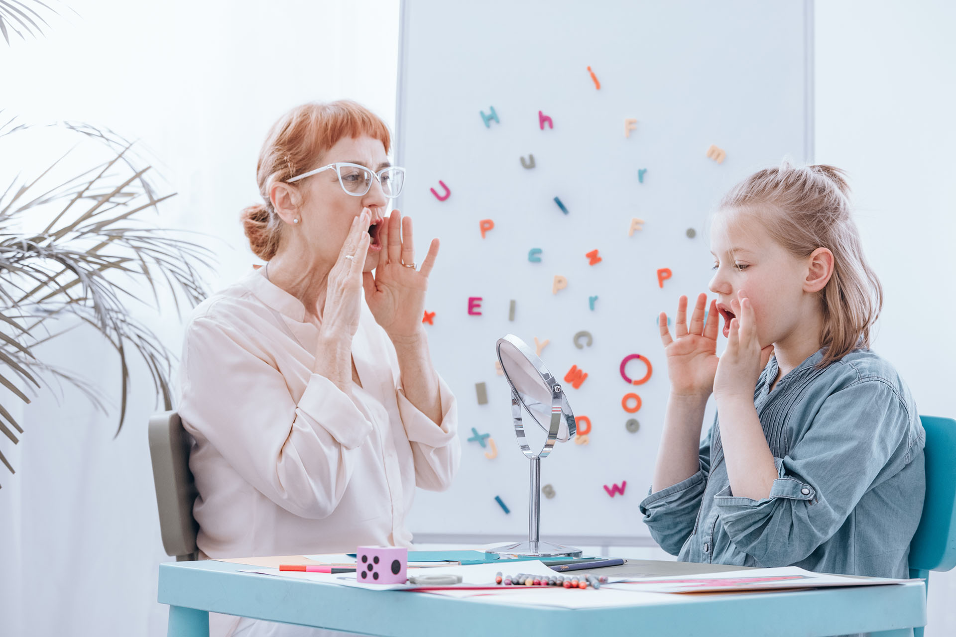 Female speech therapist helps young blonde girl with learning to speak